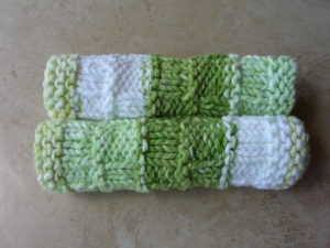 AllUnwound Seaside Spa Facecloths in green and ecru rolled up on a table