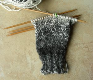 AllUnwound.com gray variegated hand knit glove on 4 double pointed wood needles