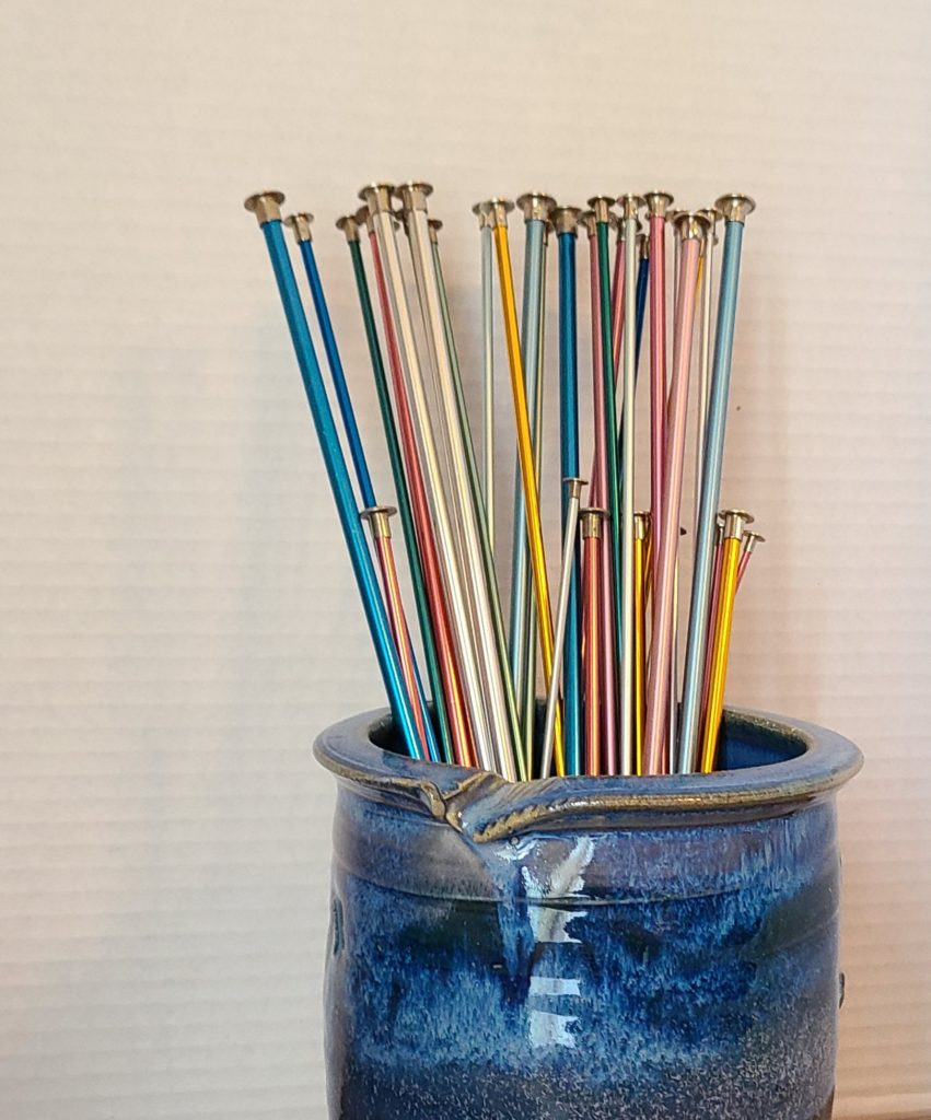 All Unwound Blue vase with knitting needles in it.