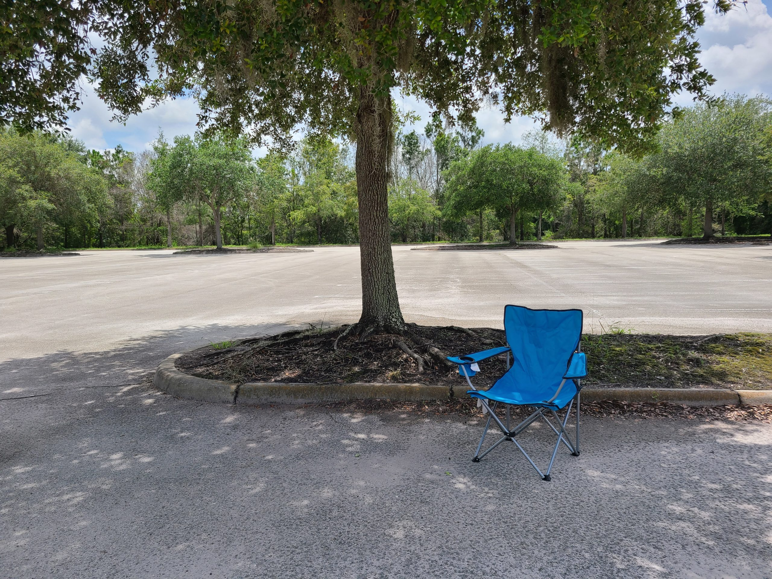 AllUnwound social distancing blue chair in empty parking lot