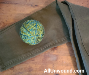 Swiss Silk in Hemlock by Handmaiden Yarn on a pair of olive jeans