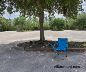 AllUnwound social distancing to the extreme, sitting outside in a blue chair in an empty parking lot.