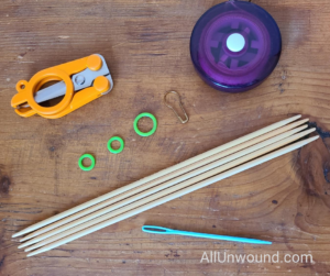Knitting tools; scissors, measuring tape, stitch markers, double pointed bamboo needles and tapestry needle