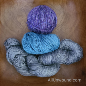 Skein of gray cake of blue and ball of purple yarn in wooden bowl