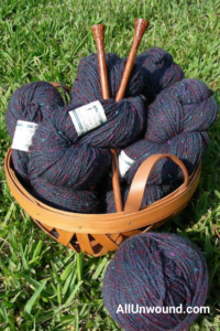AllUnwound Yarn and wooden knitting needles in basket on grass