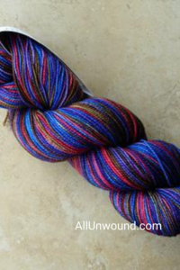 Pin size AllUnwound.com skein of berry cobbler yarn blues purples pinks