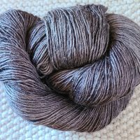 All Unwound skein of gray yarn on a hand knit item.